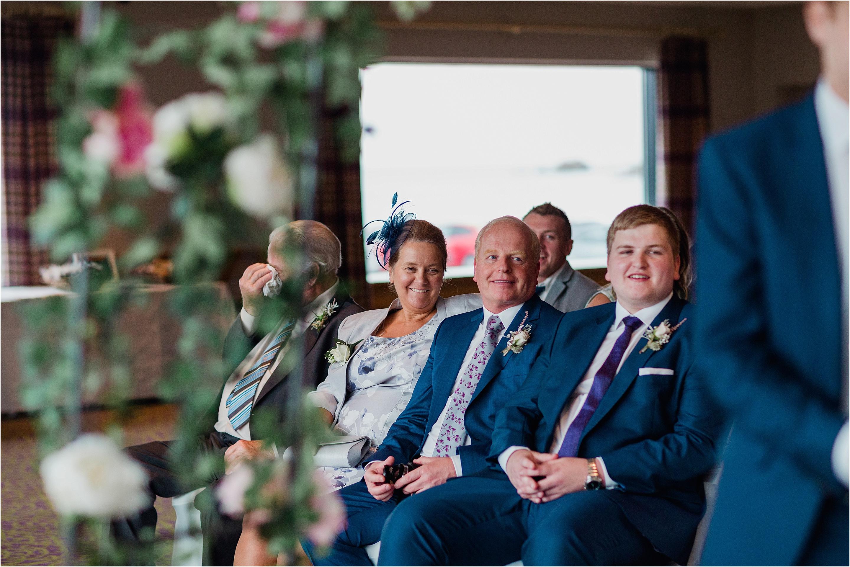 grooms parents onlooking during wedding ceremony