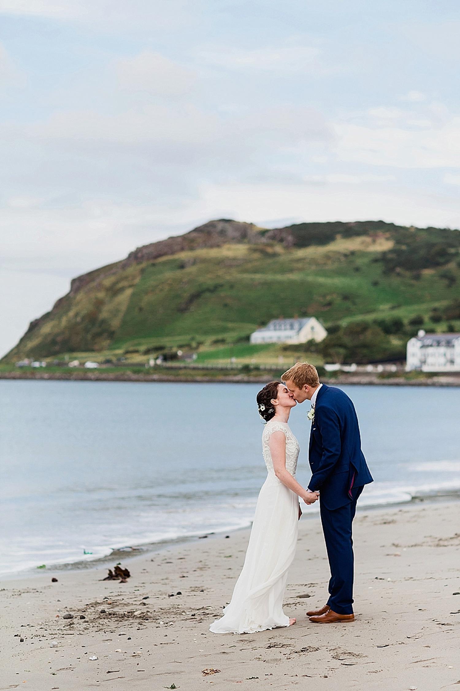 bride and groom kissing on ballygally beach
